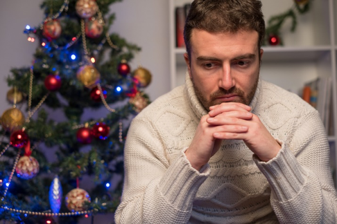 Man in front of Christmas tree with the holiday blues